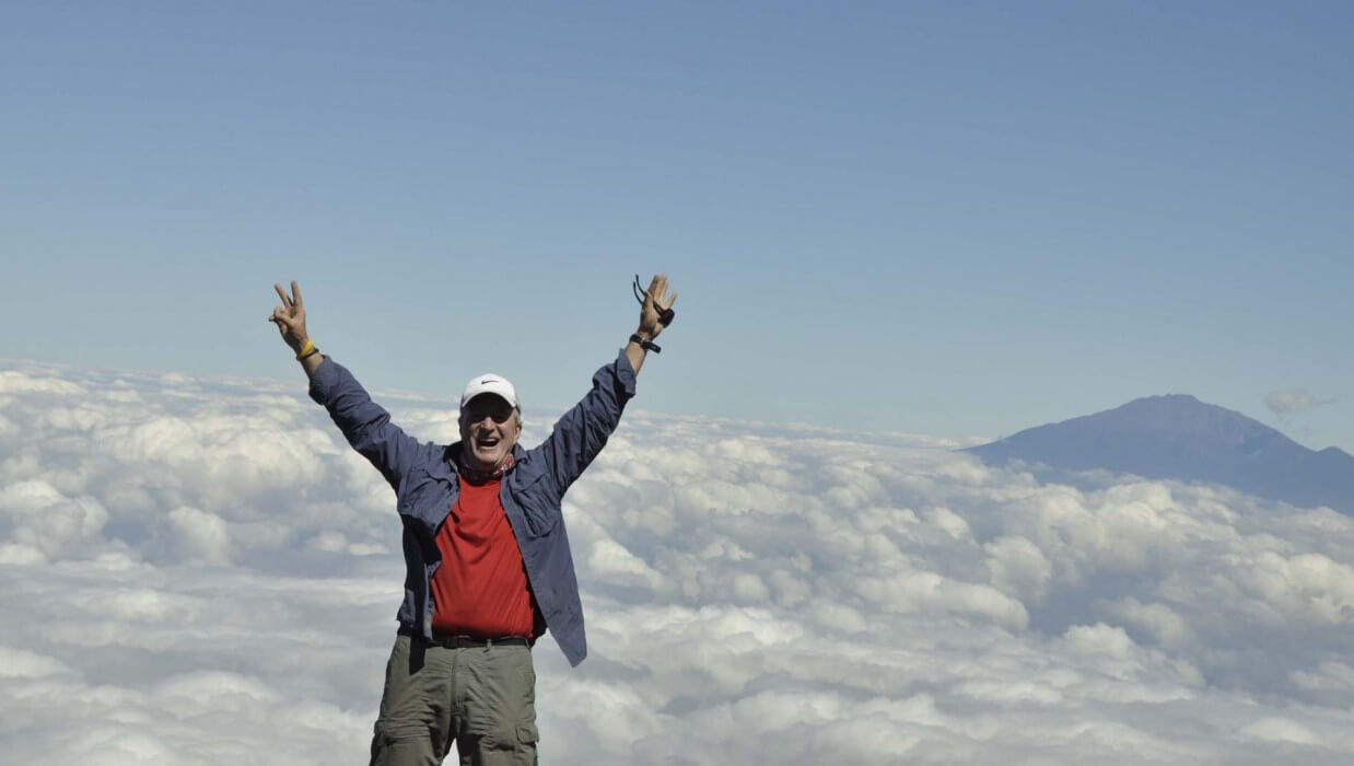 climber at the summit of mt kilimanjaro with his hands raised in the air