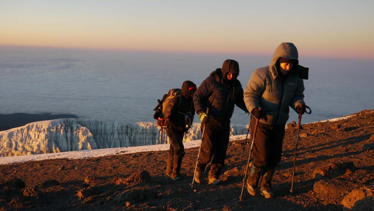 3 climbers acending mount kilimanjaro wearing cold weather gear