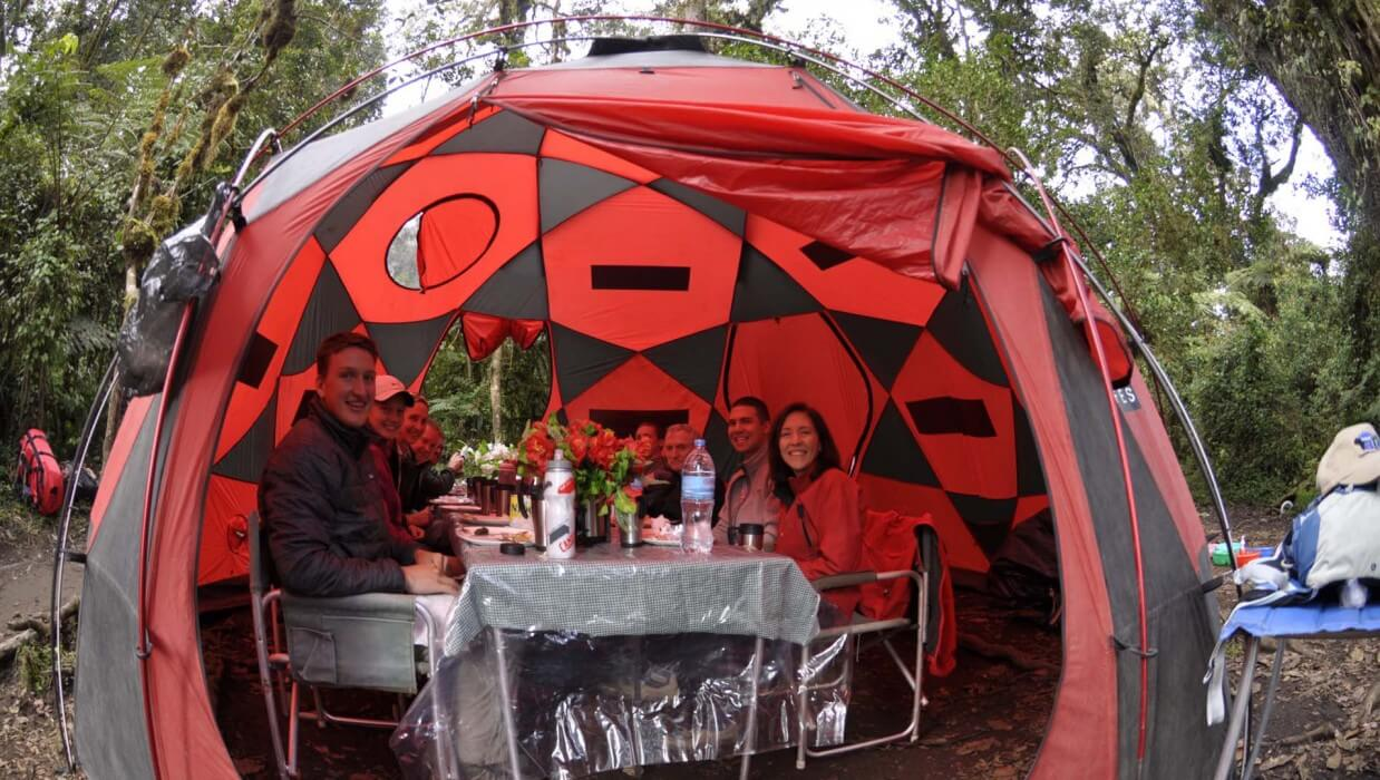 group of climbers having lunch inside a red and black tent